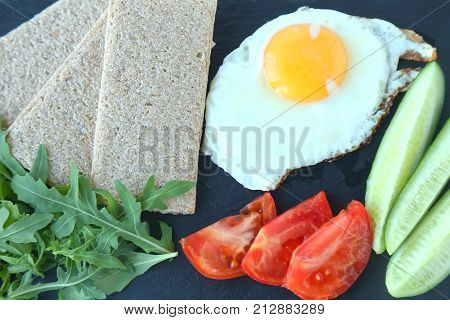 Fried egg  with cucumbers, fresh tomatoes and aragula.