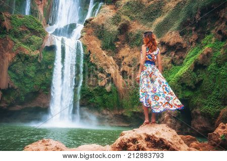 Girl In Front Of A Waterfall. Beautiful waterfall in Morocco. Back woman beautiful dress looking fall Ouzoud Grand Atlas. Exotic nature North Africa