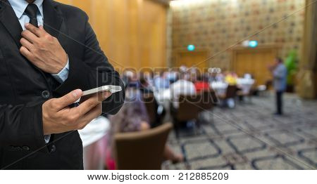 Businessman using the smart phone on the Abstract blurred photo of conference hall or seminar room with attendee background