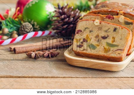 Homemade delicious soft and moist rum fruits cake or Christmas fruits cake with rich dried fruit and nuts slices on wood plate put on wood table with copy for party and celebration. Bakery concept. Christmas fruits cake or rum fruits cake.