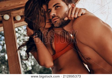 Romantic couple. Beautiful young couple in swimwear embracing while resting in the beach hut