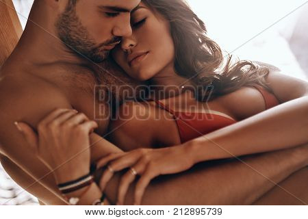 Enjoying nice weekend together. Beautiful young couple embracing while resting on the beach together
