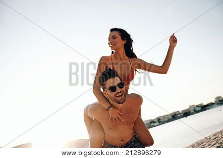 Totally in love. Handsome young man giving his attractive girlfriend a piggy back ride while spending carefree time on the beach