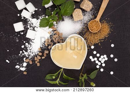 Various types of sugar from above - brown white crystal cane powdered sugar and artificial sweetener and honey in bowl. Aztec sweet herb.
