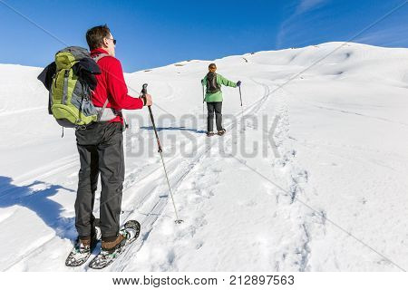 Two hikers with snowshoes in winter mountain landscape. Alps in Germany, Bavaria, Allgau.