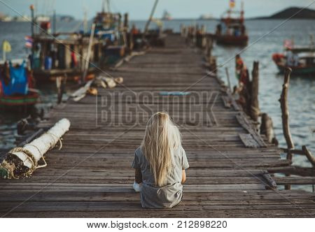 Hipster girl sitting on wooden pier in the rays of the setting sun. A vacation in Thailand. Back to the camera. Vacation in Asia