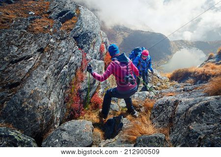 Couple of tourists in the mountains. Man helps his girlfriend to come down the rock. Young people in a mountain hike in the Himalayas.