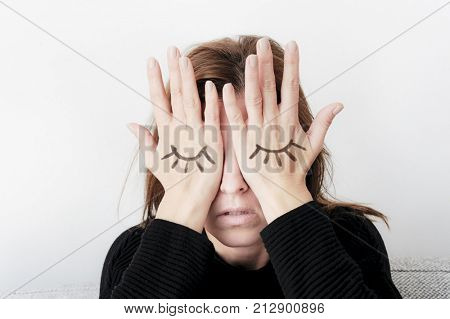 Young woman is covering her eyes with her palms. Eyes pained on her hand. Sorrow concept.