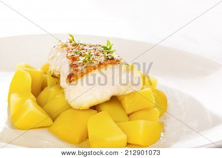 Fish fillet with potatoes on plate. Culinary seafood eating.