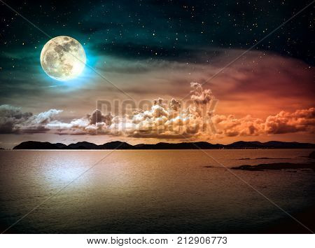 Beautiful landscape view of the sea with many stars . Attractive dark sky with cloud and full moon on seascape to night. Serenity nature background. High contrast.