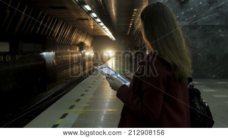 Girl in red coat using smartphone at subway or touchpad and waits for train. Woman use of cellphone and standing at city subway staton. The train arrives 4K
