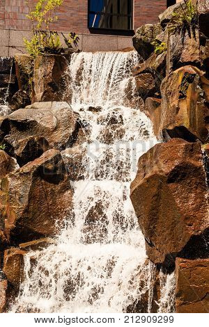 A nice landscaped waterfall over rocks in a garden