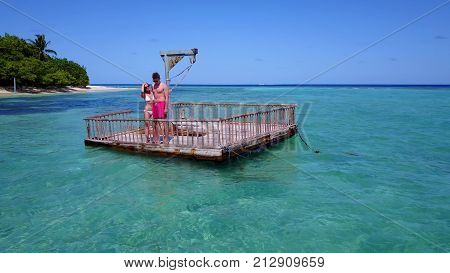two young people couple romantic sunbathing on pontoon with aerial view in beautiful clear aqua blue sea water