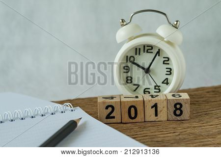 new year 2018 goals target or checklist concept as number 2018 wooden cube block with white alarm clock and paper note with pencil on wooden table.
