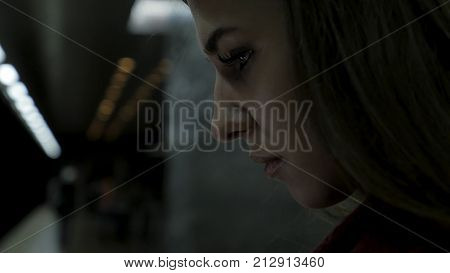 Girl using a tablet and waiting for train at subway station. brunette girl stays in subway and using touchpad. Fashionable gadget. The concept is always in touch 4K
