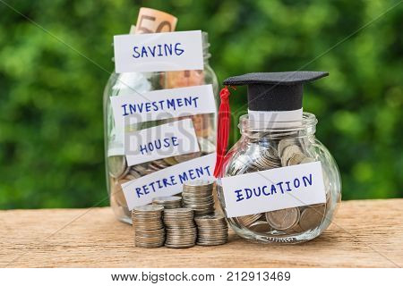 glass jar with full of coins and graduates hat label as Education with stack of coins as education or savings concept.