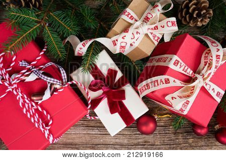 Christmas gift giving concept - christmas presents in red paper boxes with ribbons on wooden table