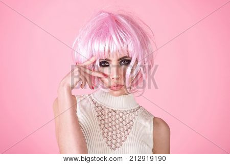 Woman wear pink wig hair on rosy background. Girl with smokey eyes makeup face. Fashion style visage. Hairdressing beauty salon. Fake false concept.