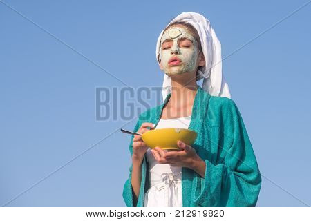 Girl in bath towel gown hold bowl. Woman with cucumber mask on face on blue sky. Skin and hair care spa wellness. Rejuvenation health youth nature. Beauty salon concept copy space
