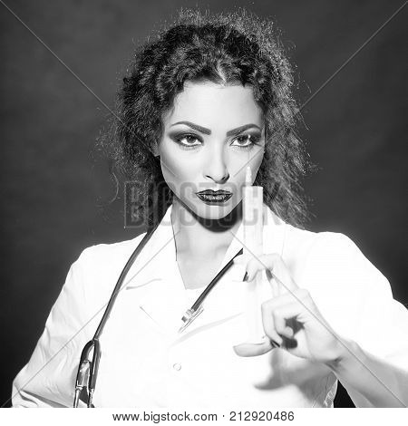 Closeup view portrait of one serious sexual beautiful brunette medical worker with stethoscope in white nurse uniform holding injecting suringe for botox shot or drugs in studio square picture