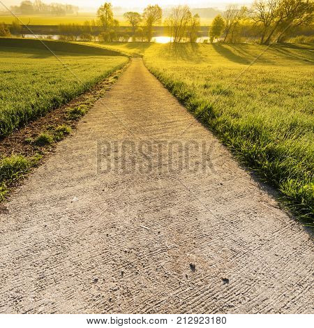 Swiiss landscape with meadows along the irrigation canal at sunrise. Asphalt path descending to the hotspot on the water between meadows in Switzerland