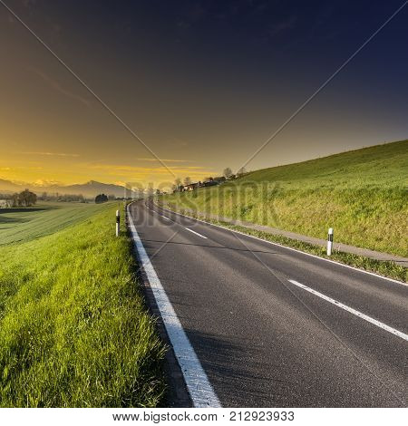 Asphalt road along the dike. Pasture on the background of Alps in Switzerland at sunset. Swiss landscape with meadows along the irrigation canal.