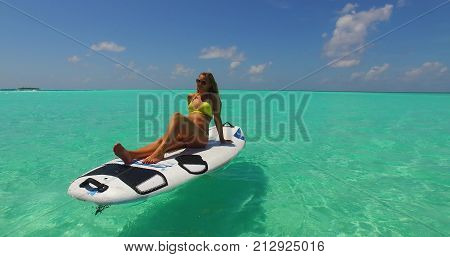 one 1 beautiful young girl in bikini sunbathing on surfboard paddleboard and relaxing by the aqua blue sea water on white sand in the sun