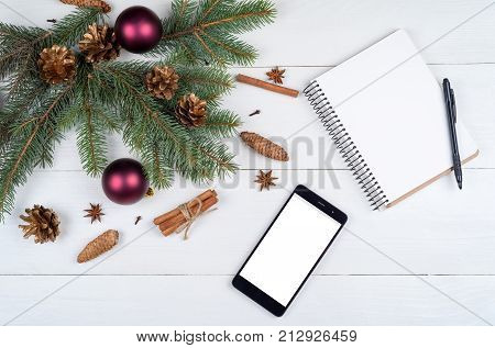 Christmas background with red gift boxes mobile phone with white screen and blank notebook copy space. Template for new year goal or resolutions. Christmas mockup. Flat lay top view