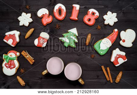 Christmas background with happy new year 2018 sign symbol gingerbread cookies and two cups of cocoa cones cinnamon sticks and star anise. Flat lay top view. Christmas cookies
