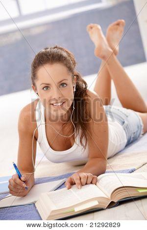 Attraktive junge weibliche Studium zu Hause, Stock, Handauflegen lächelnd.?