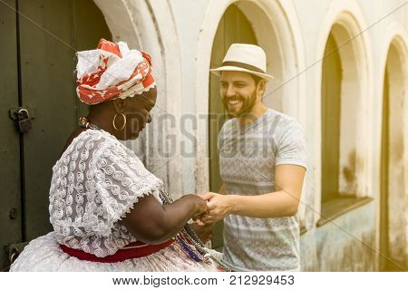 Tourist dancing with 'Baiana' woman in Pelourinho, Salvador, Bahia, Brazil