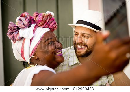 Tourist taking selfie photos with 'Baianas' women in Pelourinho, Salvador, Bahia, Brazil