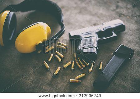 Gun, Gun with ammunition on wooden background.