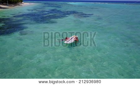 2 pretty young girls on a surfboard paddleboard with aerial view in warm blue sea water