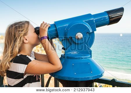 Blond Caucasian school girl is looking through a stationary paid telescope stands on sea coast poster