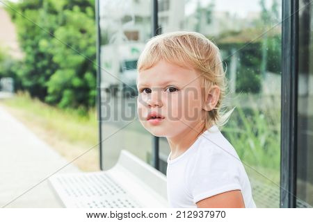 Sad Caucasian Blond Baby Girl Waits On A Bench