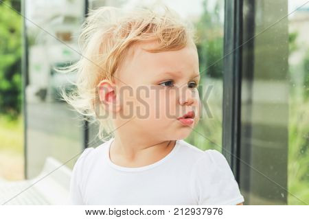 Cute Caucasian Blond Baby Girl On A Bus Stop