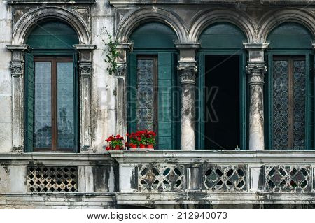 Ancient balcony in Venice, Italy. Venetian architecture. Red flowers in pots against background of a vintage building in Venice, Italy. Venetian balcony. Red flowers on an old balcony without people.