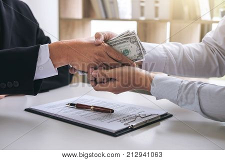 Bribery and corruption concept bribe in the form of dollar bills Businessman shaking hands and giving hides money while making deal to agreement a contract.