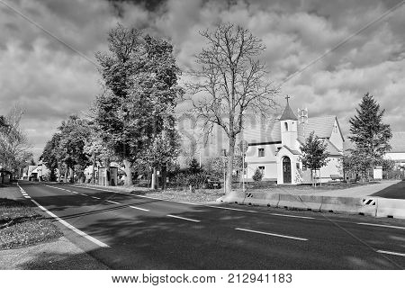 Okna, Litomerice District, Czech Republic - October 13, 2017: Autumnal Village Green With Road In Fo