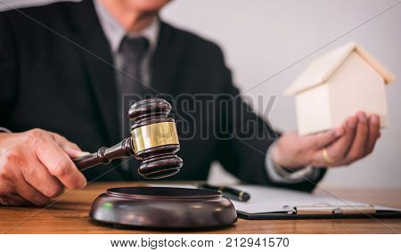 Male lawyer or judge hand's striking the gavel on sounding block working at courtroom for decide home insurance Law and justice concept Settle a house dealing lawsuit.