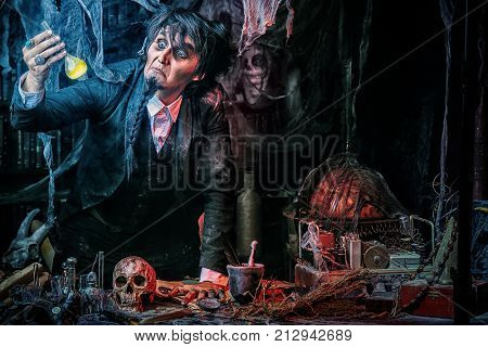 Medieval scientist creates a magical elixir in his laboratory. Alchemist. Halloween.