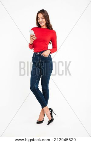 Full length portrait of a happy satisfied asian woman texting on mobile phone while standing isolated over white background