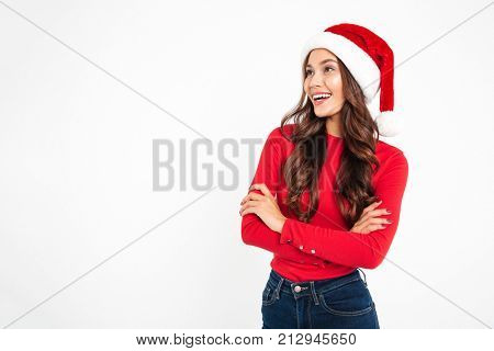 Portrait of a beautiful friendly asian woman dressed in red santa hat standing with arms folded and looking away at copy space isolated over white background