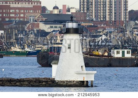 New Bedford Massachusetts USA - November 1 2017: Palmer's Island lighthouse against background of fishing vessels and downtown buildings along New Bedford waterfront