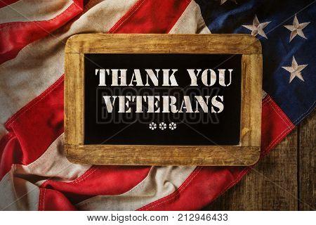 Celebration of Veterans Day. Close-up of USA flag in grunge design with wooden blackboard. Motive of celebration 11th of November