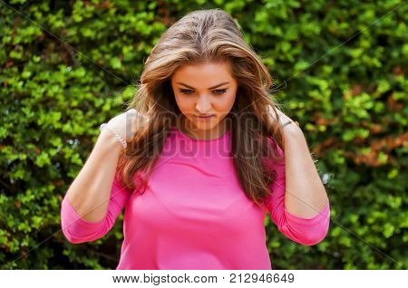 Attractive Caucasian girl with gorgeous hair looking down with green natural background.