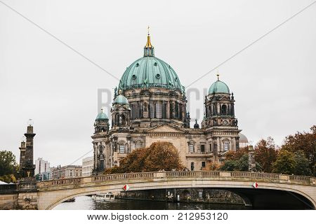Beautiful old building in the style of neoclassicism and baroque with cross and sculptures near the river and bridge