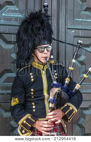 EDINBURGH SCOTLAND - May 26th 2017: Edinburgh street bagpiper at Edinburgh castle Edinburgh Scotland May 26 2017. The bagpipe players are a major tourist attraction in Scotland.