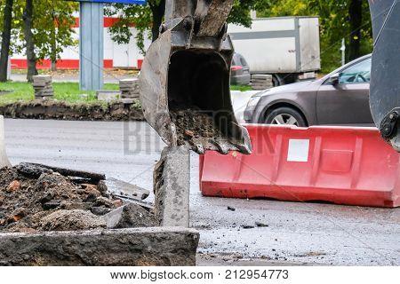 excavator removes road asphalt on the roadway